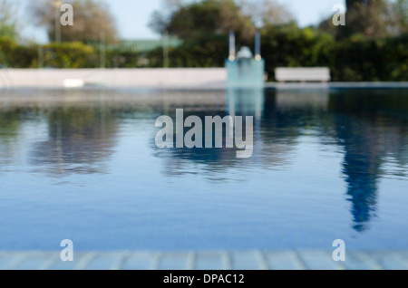 Swimming pool taken from low position with blurred background - Stock Image