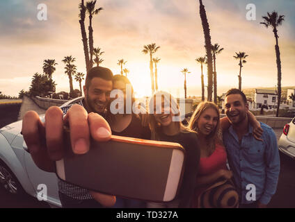 Happy friends standing in front of convertible car and taking selfie with mobile phone camera - Young millennial people having fun on roadtrip - Stock Image