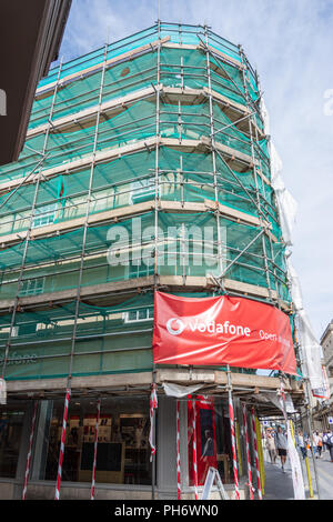 The door and window of the Vodafone shop in Bath with the building surrounded by scaffolding and green netting and a large open as usual sign - Stock Image