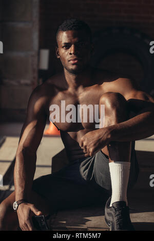 Strong afroamerican athletic man with naked perfect shape muscular body looking at camera isolated over brick background. - Stock Image