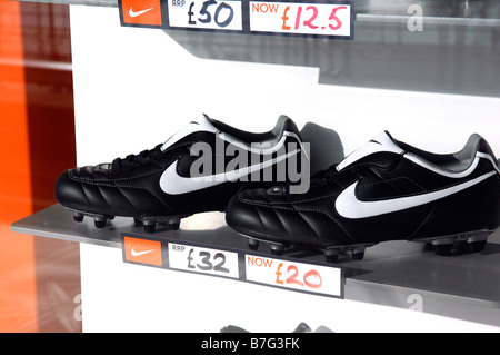 nike footwear football boots soccer shoes window display reduced american company fashion retail shop store niketown - Stock Image