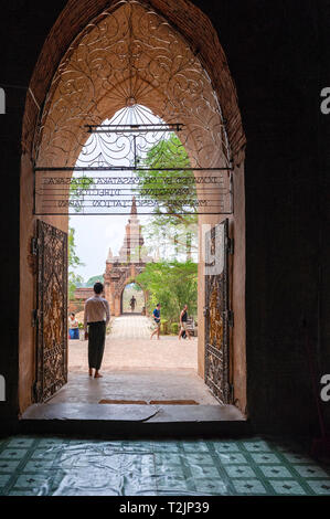 Tourguide standing at the entrance to a temple in Bagan Myanmar (Burma) - Stock Image