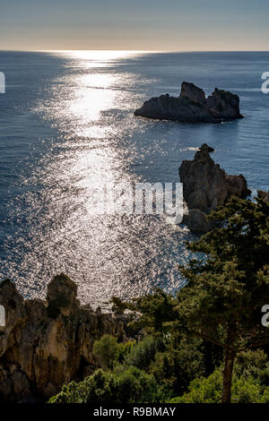 Calm spring day, sunlight path formed by Sun light reflection in the crystal clear water of Ionian sea, Corfu, Kerkyra island, Greece. Few smile islan - Stock Image