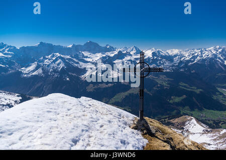 Cross on the snow-covered summit of Rossstock (2461m). In the background panorama of many summits of the Swiss Alps. - Stock Image