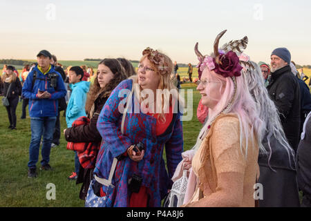 Stonehenge, Amesbury, UK, 21st  June 2018,   2 women looking through towards the stones and sunrise at summer solstice  Credit: Estelle Bowden/Alamy Live News. - Stock Image