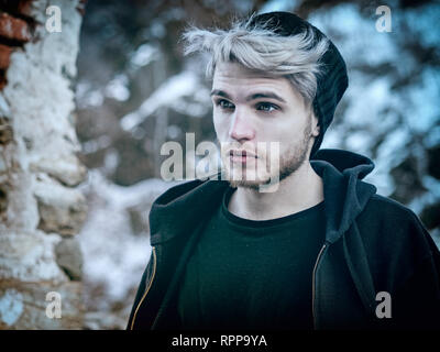 Handsome man in snow posing for camera - Stock Image