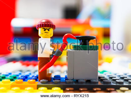 Poznan, Poland - March 14, 2019: Lego thief trying to open a safe with a crowbar. - Stock Image