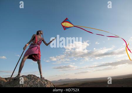 A Maasai Warrior flies a kite over the Rift Valley. Kenya, Africa. - Stock Image