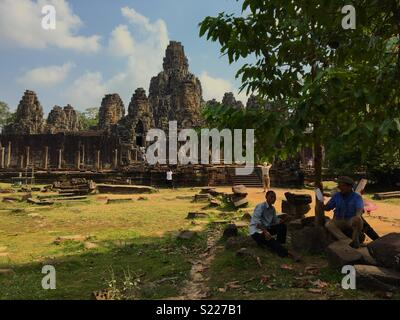 People resting under Tree in the shade on a hot day at Angkor Wat in Cambodia - Stock Image
