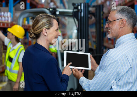 Warehouse manager and client discussing over digital tablet - Stock Image