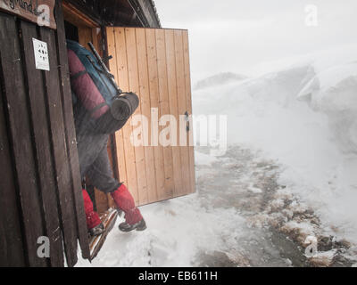 man with heavy pack entering an emergency hut in a snowstorm - Stock Image