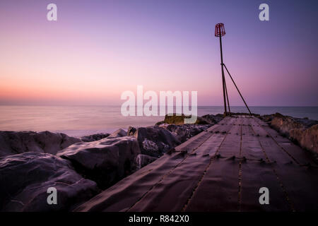 rocky outfall into the ocean at sunrise - Stock Image