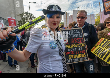 London, UK. 20th October 2018. A woman dressed as a police officer holds a baton and a poster. People gather with placards, banners and flags at Hyde Park Corner for the People's Vote March calling for a vote to give the final say on the Brexit deal or failure to get a deal. They say the new evidence which has come out since the referendum makes it essential to get a new mandate from the people to leave the EU. Peter Marshall/Alamy Live News - Stock Image