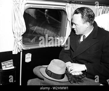 Man seated in an airplane looking out a window  ca. 1936 - Stock Image