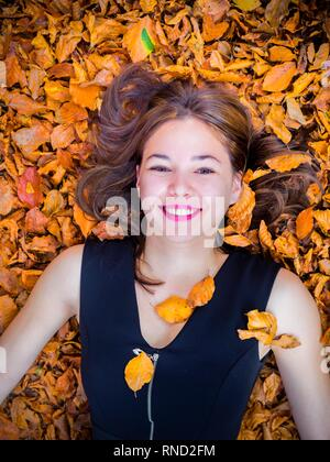 Pretty teen girl is smiling at camera view directly from above - Stock Image