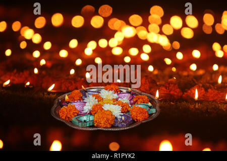 A plate of lamps and marigold flowers for hindu ritual kept on a lawn with other lamps, during Diwali festival in India. - Stock Image