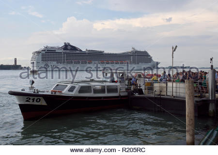 Passengers board a water bus as the MSC Magnifica passes out of the Venetian lagoon: Venice. - Stock Image