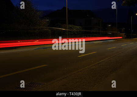 Abstract photo of nighttime traffic. You can see colorful light lines in a dark environment. Photographed in Nyon, Switzerland during springtime. - Stock Image