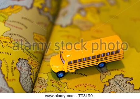 Siku toy classic yellow school bus on a page with map from a atlas book on circa June 2019 in Poznan, Poland. - Stock Image