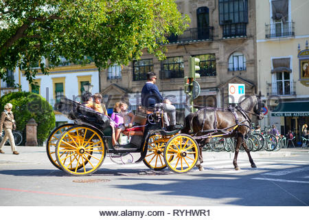 Family riding in a horse drawn carriage in Seville - Stock Image