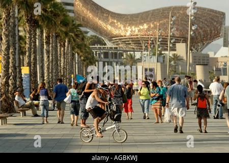 Spain Barcelona beach Platja de la Barceloneta promenade people background fish sculture by Frank Gehry - Stock Image