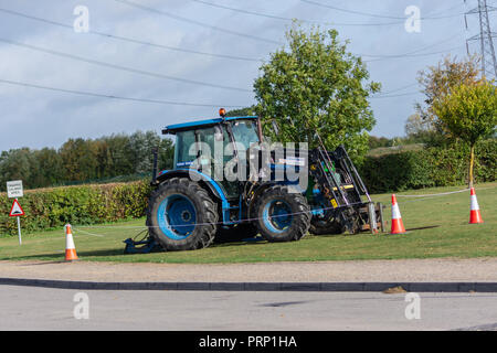 A blue John Deere tractor with Balfour Beatty stickers parked on grass in an area cordoned off with rope and traffic cones - Stock Image
