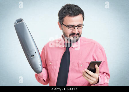 Cheerful young man using a vacuum cleaner looking in his mobile phone - Stock Image