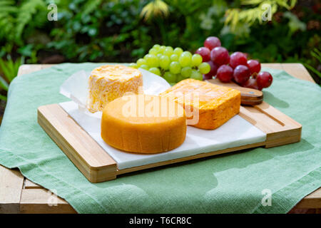 French cheeses collection, Riche de Saveurs, Langres and Le peche des bons peres cheeses served with grapes on white marble plate outdoor in green gar - Stock Image