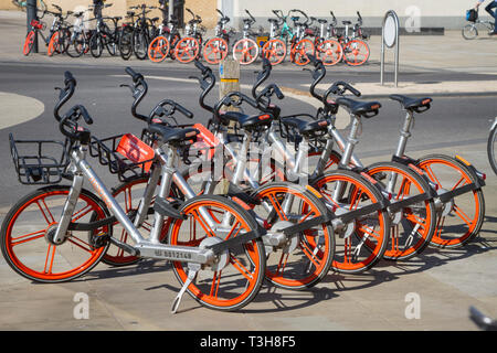 Mobikes for hire in racks outside Oxford Railway Station - Stock Image