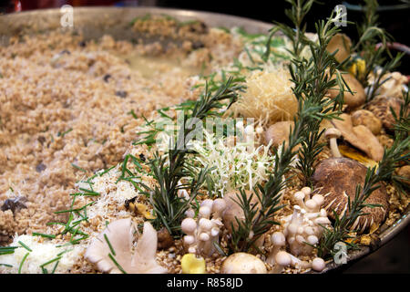 Wild mushrooms and rosemary cooking in spelt risotto at Borough Market Christmas hot food stall in London England UK  KATHY DEWITT - Stock Image