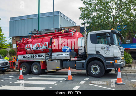 Jet Aire contractor worker maintenance cleaning of roadside drains from a vacuum tank lorry - Stock Image