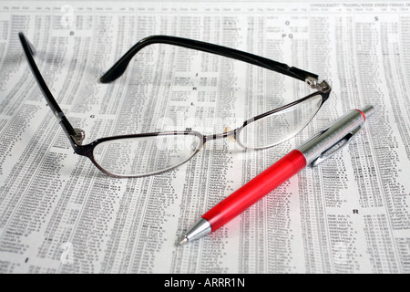 Eyeglasses and pen on newspaper financial page - Stock Image