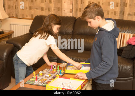 young children siblings playing a board game, boy twelve, girl three - Stock Image