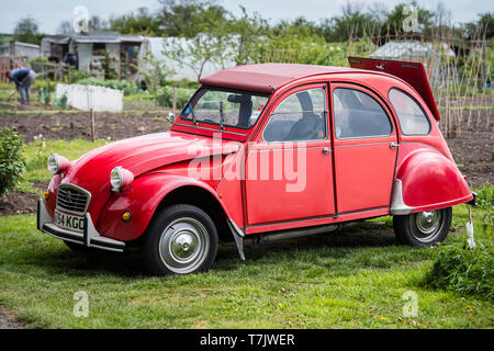 An immaculate red Citroen 2CV6 Special parked on an allotment in England UK. - Stock Image