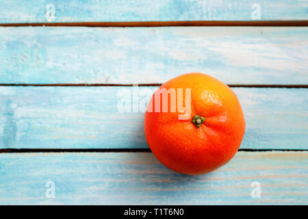 Simple composition of one mandarin and retro Light blue wood plank surface texture, wooden board background with copy space - Stock Image