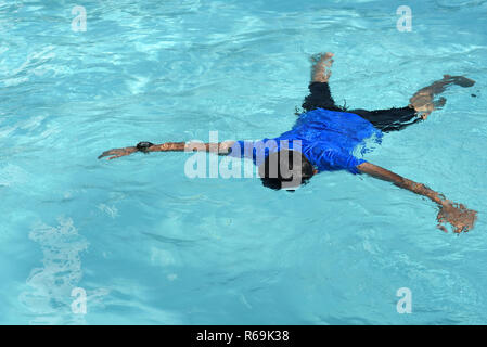 floating body of a drowned male children in swimming pool. concept of safety - Stock Image