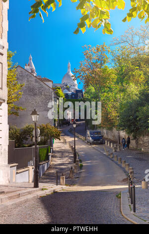 Cozy old street and Sacre-Coeur Basilica at the sunny summer morning, quarter Montmartre in Paris, France - Stock Image