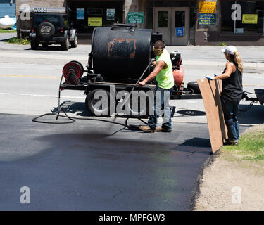 Workers spraying sealant on a driveway in Speculator, NY USA - Stock Image