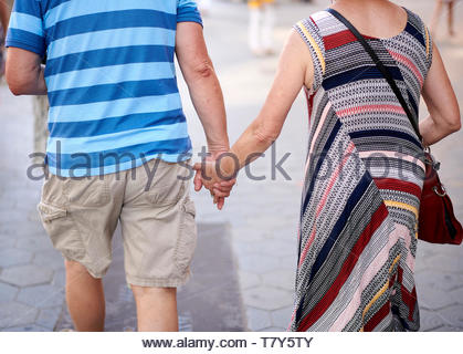 Couple walking and holding hands on  Street in the City of Barcelona in Catalunya in Spain in Europe - Stock Image