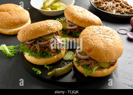 Tasty pulled beef sandwiches with vegetables on wooden board. Close up view - Stock Image
