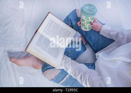 Young student girl reading book in cozy bed and holding book on legs with bare feet and drinking hot coffee in retro cup. Relaxation and education - Stock Image