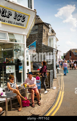 UK, Cornwall, Padstow, The Strand, visitors in sunshine outside waterfront ice cream shop - Stock Image