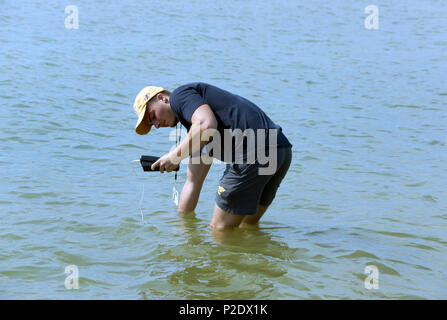 Man testing  water temperature, quality at Lake Michigan beach  for Wisconsin Department of Natural Resources, local health agencies Two Rivers, WI - Stock Image