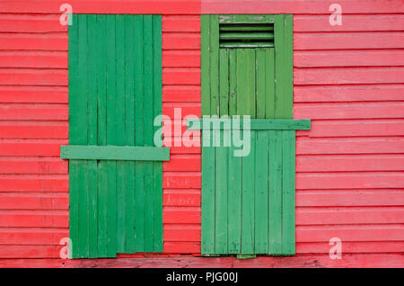 The rear of a red and green beach hut at St. James Beach near Capetown, South Africa. - Stock Image