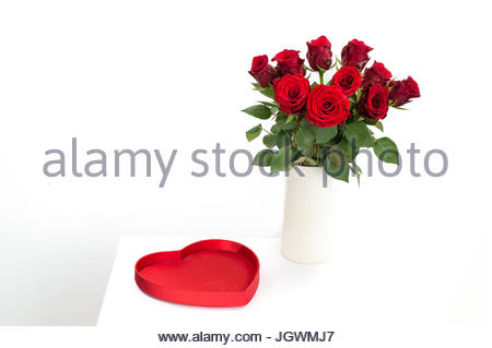 Red roses bouquet in white vase with red heart - Stock Image