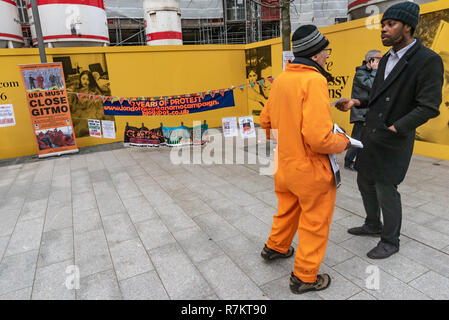 London, UK. 10th December 2018.  A protester talks with a man passing by at the US Embassy in the final 'Shut Guantanamo!' monthly protest of 2018 on the 70th anniversary of the Universal Declaration of Human Rights (UDHR). This declared 'No one shall be subjected to torture or to cruel, inhuman or degrading treatment or punishment' and 'No one shall be subjected to arbitrary arrest, detention or exile.' Guantanamo still has 40 detainees who have been tortured and held in indefinite detention without trial for almost 17 years. Credit: Peter Marshall/Alamy Live News - Stock Image