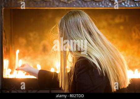 Girl with blonde hairs light a candle in church - Stock Image