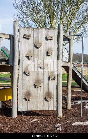A childrens wooden climbing wall with large easy hand and footholds in a childs playground area - Stock Image
