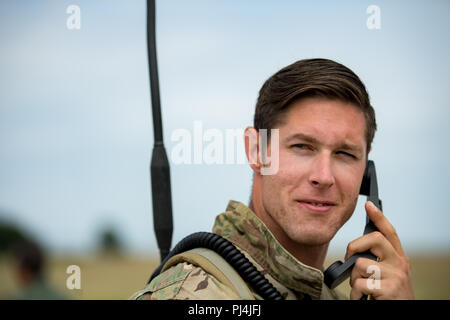 U.S. Air Force Tech. Sgt. Craig Reinwald, 435th Contingency Response Squadron contingency air traffic controller, listens to his radio at Boboc Air Base, Romania, Aug. 23, 2018. Reinwald and his team provided ground support for the 37th Airlift Squadron pilots dropping Romanian air force paratroopers out of C-130J Super Hercules aircraft as part of exercise Carpathian Summer 2018. (U.S. Air Force photo by Senior Airman Devin Boyer) - Stock Image