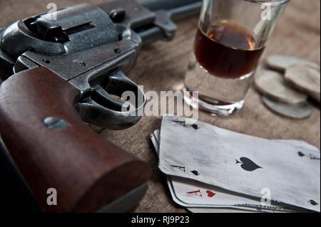 alter Revolver auf einer Holztheke mit Spielkaten, Geld und Alkohol, - Stock Image
